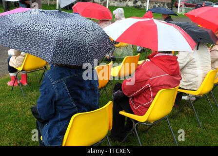 Menschen unter bunten Sonnenschirmen sitzen auf gelben Kunststoff Stühle - Stockfoto