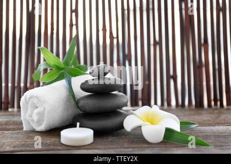Wellness Steine mit Handtuch, Bambus, Kerze und tropische Blume auf hölzernen Hintergrund - Stockfoto