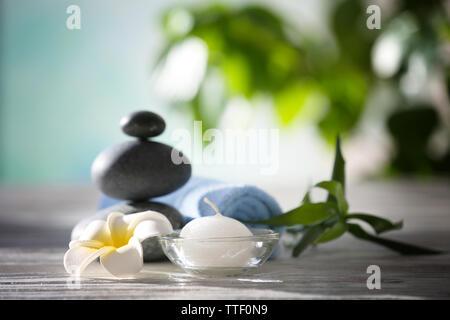 Wellness Steine mit Handtuch, tropische Blume, Bambus und Kerze auf unscharfen Hintergrund - Stockfoto