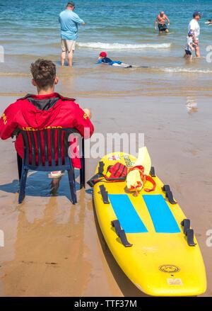 Junge männliche Rettungsschwimmer, in einem Stuhl aus Kunststoff sitzt auf einem Strand am Meer, mit Menschen im Meer an einem heißen Tag in Sheringham, Norfolk, England, UK. - Stockfoto