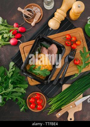 Hohe Betrachtungswinkel gebackenes Fleisch in Container mit Gemüse auf Tisch - Stockfoto