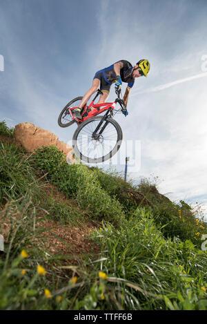 Mountainbike Downhill Springen auf seinem Fahrrad über Gras - Stockfoto