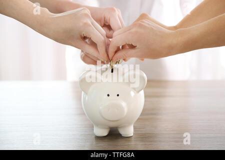 Hände die Münze in piggy Bank am Tisch - Stockfoto