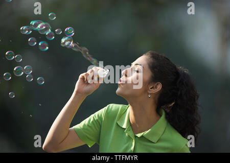 Junge Frau bläst Seifenblasen - Stockfoto
