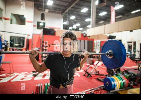 Frau mit Langhantelstange mit Hantelscheiben in Fitnesscenter Stockfoto