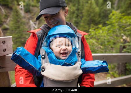 Die Mutter ihre Tochter glücklich in Baby carrier beim Wandern. - Stockfoto