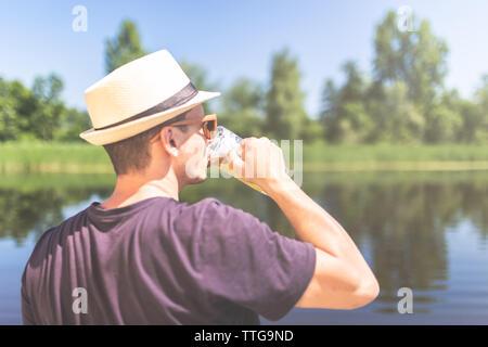 Ansicht der Rückseite des jungen Mann mit Strohhut und trinken Bier vor der wunderschönen Natur. - Stockfoto