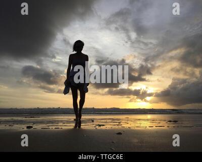 Sorglos Frau Wandern am Strand gegen Himmel bei Sonnenuntergang - Stockfoto