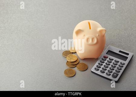 Beige Sparschwein mit Münzen und Taschenrechner auf grauem Hintergrund - Stockfoto