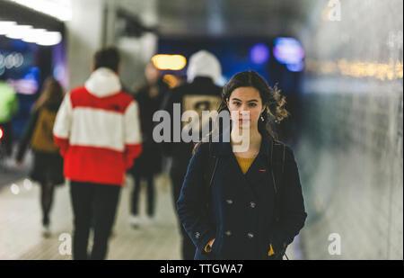 Müde junge womanwith Rucksack ist zu Fuß auf der U-Bahn Station in Abend Stockfoto