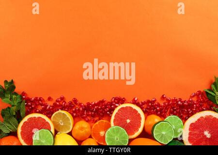 Satz von aufgeschnittenen Zitrusfrüchten mit Granatapfel Samen auf orangefarbenem Hintergrund - Stockfoto