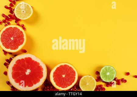 Satz von aufgeschnittenen Zitrusfrüchten mit Granatapfel Samen auf gelbem Hintergrund - Stockfoto