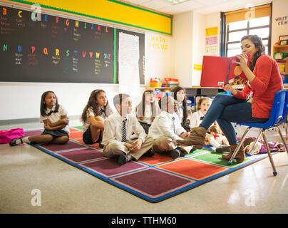 Lehrer zeigt Bild Buch für Studenten im Klassenzimmer