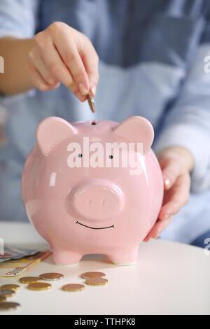 Weibliche Hand Münze in piggy Bank - Stockfoto