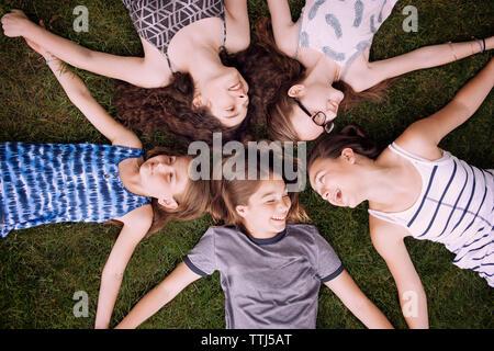Hohe Betrachtungswinkel von Freunden liegen auf Gras - Stockfoto
