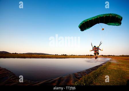 Man parasailing über den See gegen den klaren Himmel - Stockfoto