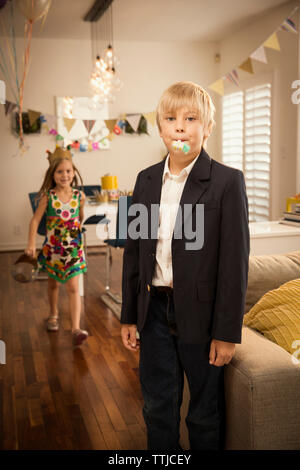 Portrait der Junge stehend mit Schwester wandern im Hintergrund zu Hause - Stockfoto