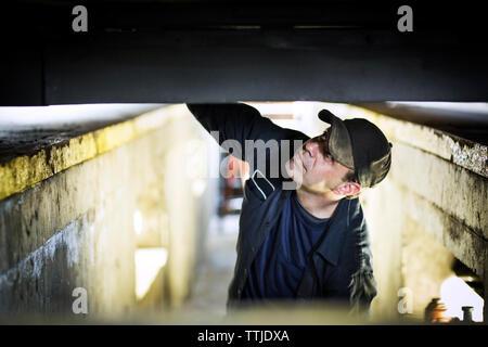 Portrait von Mechaniker sitzen auf Gabelstapler in Werkstatt - Stockfoto