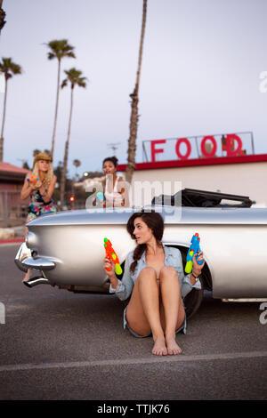 Freunde spielen mit Squirt gun mit dem Auto auf der Straße - Stockfoto