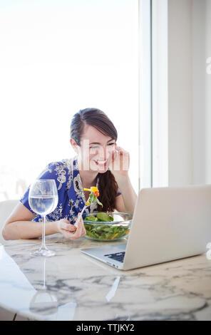 Lächelnde Frau mit Laptop beim Frühstück - Stockfoto