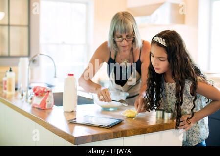 Enkelin und Oma Essen zubereiten, während im Tablet Computer Küche suchen - Stockfoto