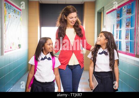 Lehrer mit Schülern zu Fuß im Korridor - Stockfoto