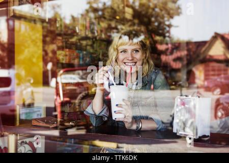 Glückliche Frau weg schauen, während Milchshake Glas Holding im Cafe - Stockfoto