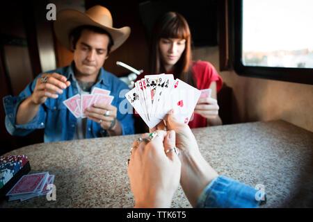In der Nähe von Frau mit Karten, beim Spielen mit Freunden im Wohnmobil - Stockfoto