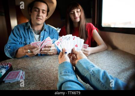 Zugeschnittenes Bild der Frau mit Karten, beim Spielen mit Freunden im Wohnmobil - Stockfoto