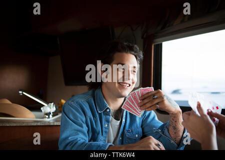 Glückliche Menschen, die Karten mit Freundin im Wohnmobil sitzen van - Stockfoto