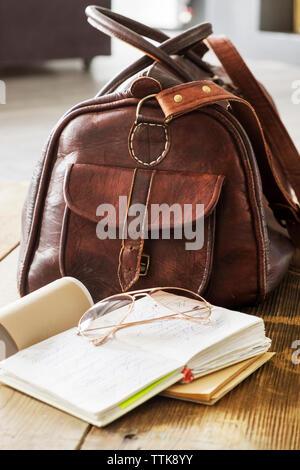 Ledertasche und Bücher auf dem Tisch zu hause Büro Stockfoto