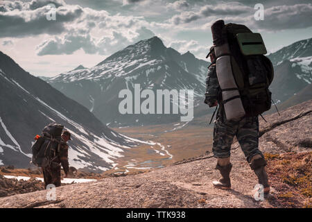 Wanderer mit Rucksack zu Fuß auf den Berg gegen bewölkter Himmel im Winter - Stockfoto