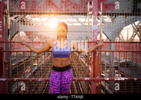 Portrait von zuversichtlich Sportlerin stehend gegen Zaun auf Brücke - Stockfoto