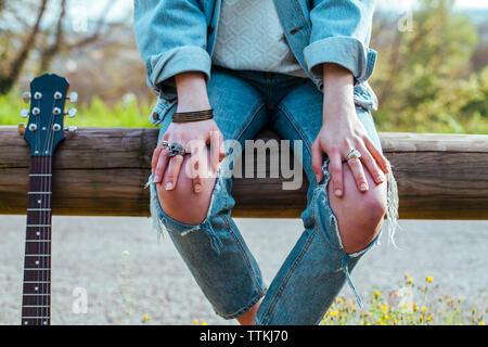Mittelteil der Frau mit Gitarre tragen zerrissene Jeans beim Sitzen auf hölzernen Geländer gegen See im Park - Stockfoto