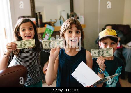 Portrait von Happy Geschwister zeigen uns, Papier, Währung zu Hause - Stockfoto