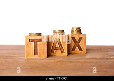 Steuerkonzept mit Holzwürfeln und Münzen, isoliert auf weißem - Stockfoto