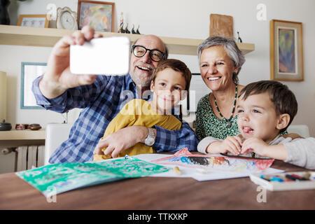 Fröhlicher älterer Mann unter selfie mit der Familie zu Hause. - Stockfoto