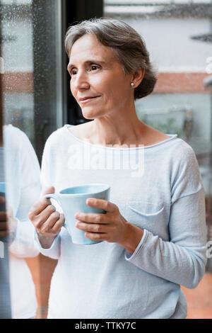Nachdenklich reife Frau mit Kaffeetasse, während durch das Fenster zu hause suchen - Stockfoto