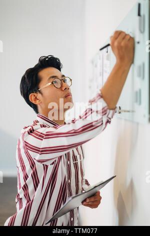 Ernsthafte Geschäftsmann holding Zwischenablage beim Schreiben auf der Tafel im Büro - Stockfoto
