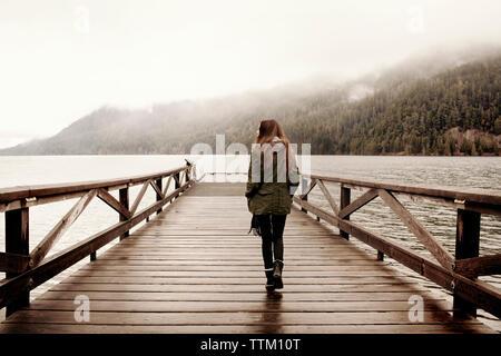 Ansicht der Rückseite Frau zu Fuß auf der Promenade am See bei Nebel - Stockfoto
