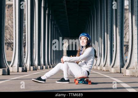 Portrait von Frau über Skateboard sitzen auf der Straße unter der Brücke - Stockfoto