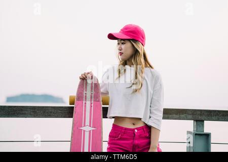 Nachdenkliche Frau mit Skateboard stehend gegen klaren Himmel auf Brücke - Stockfoto