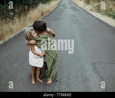 Bruder küssen Schwester beim Stehen auf Landstraße - Stockfoto