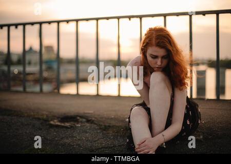 Portrait von nachdenklich junges Mädchen sitzt auf Bridge bei Sonnenuntergang Stockfoto
