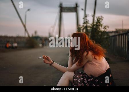 Junge rothaarige Frau rauchen Zigarette beim Sitzen auf der Brücke