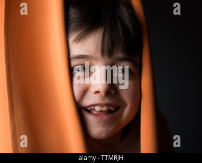 Portrait einer jungen Happy Boy peeking seinen Kopf durch Vorhänge.