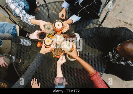 Hohe Betrachtungswinkel von Freunden toasten Getränke beim Sitzen am Tisch im Hinterhof - Stockfoto