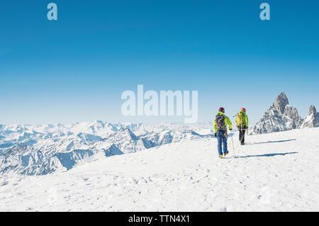 Ansicht der Rückseite des Wanderer Wandern auf schneebedeckten Berg gegen den klaren blauen Himmel - Stockfoto
