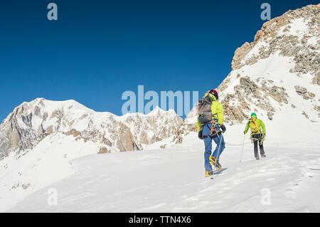 Ansicht der Rückseite des Wanderer mit Rucksack klettern Berg gegen den klaren blauen Himmel während der sonnigen Tag - Stockfoto