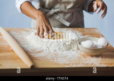Mittelteil der Frau kneten den Teig auf dem Tisch beim Stehen in der Küche Stockfoto